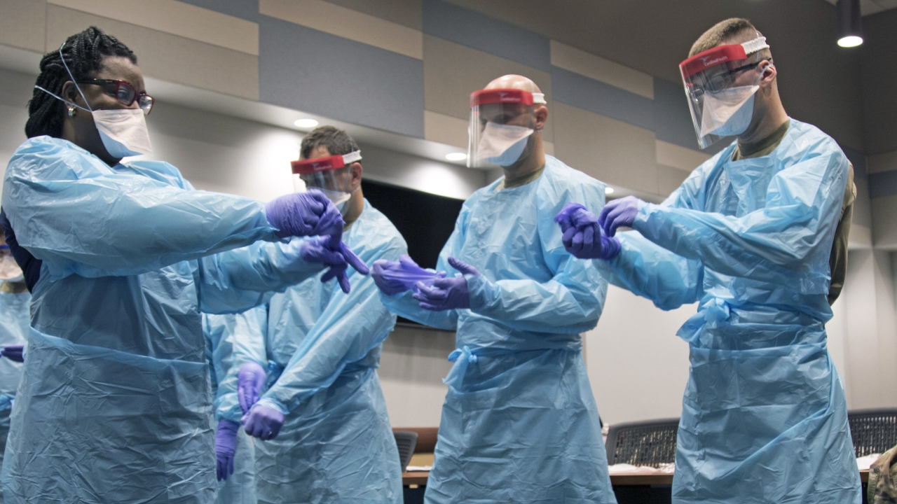 Members of the Florida National Guard (FLNG) gather with local hospital staff to collaborate on donning and doffing personal protective equipment (PPE) during Task Force – Medicals' response to the COVID-19 virus, March 17, 2020